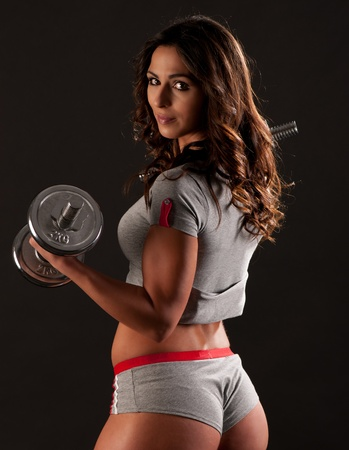 face lift: Young fit girl working out with weights - Portrait of pretty young woman lifting dumbbells during exercising
