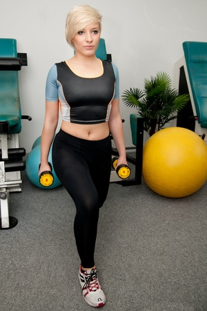Beautiful young woman working out in fitness club Stock Photo - 12435006