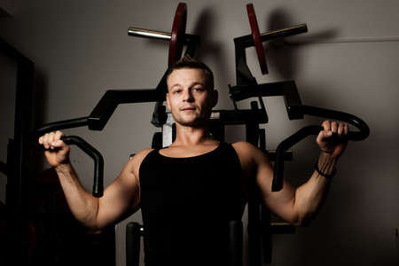Man doing fitness training on machine with weights in a gym Stock Photo - 13232907
