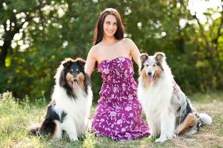 Young woman taking two collies on a walk photo