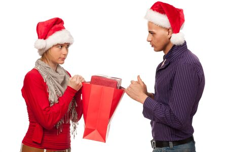 Girl and man with santa hat fighting for a present