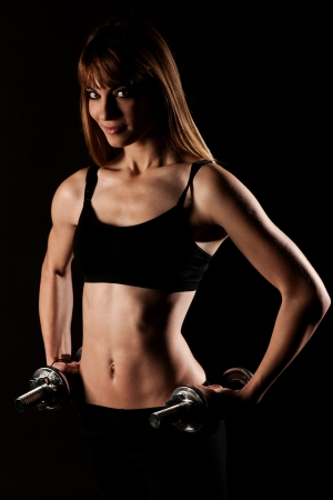 Young fit girl working out with weights - Portrait of pretty young woman lifting dumbbells during exercising photo