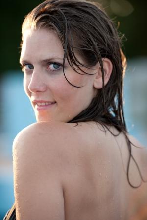 Cute brunette girl in bikini swimwear in swimming pool photo
