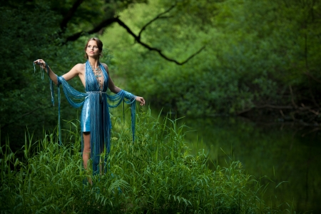 attractive young woman with fashionable garment in swamp photo