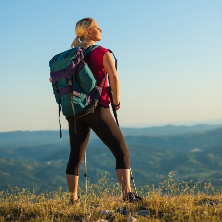 Woman on trekking - Beautiful blonde girl hiking on mountains photo