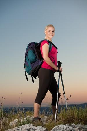 Woman on trekking - Beautiful blonde girl hiking on mountains photo