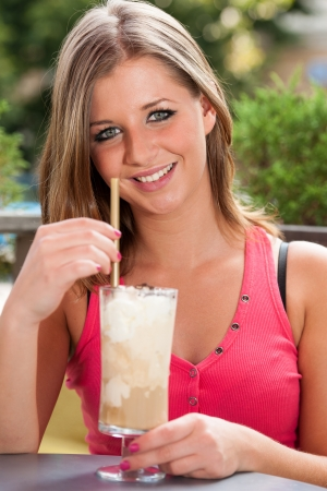 Young girl drinking ice coffee photo