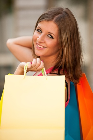 Girl carriing vibrant shopping bags outdoor photo