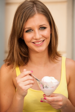 Attractive young woman eating ice cream photo
