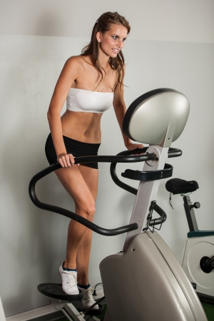 Beautiful slim girl work out on stepper in fitness