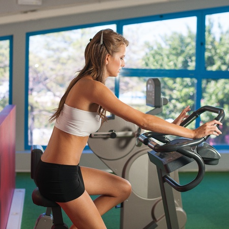 skinny woman: Beautiful active skinny woman riding a bike in fitness
