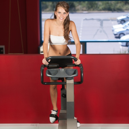 Beautiful active skinny woman riding a bike in fitness photo