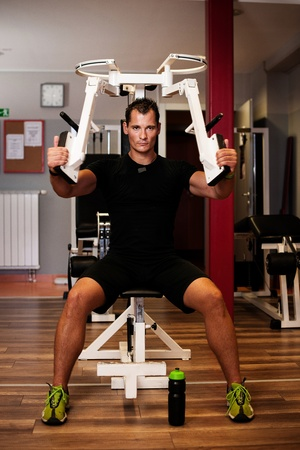 Active sportsman works out hard in fitness on butterfly machine photo