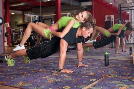 Man doing pushups with preety giro on hus back in fitness photo