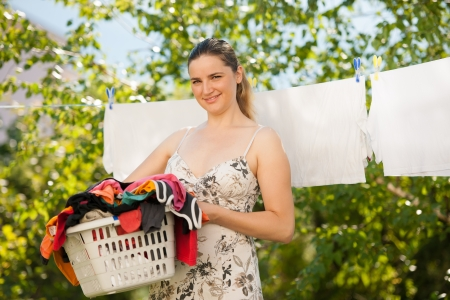 clothes line: Young beautiful woman hanging laundry outdoor