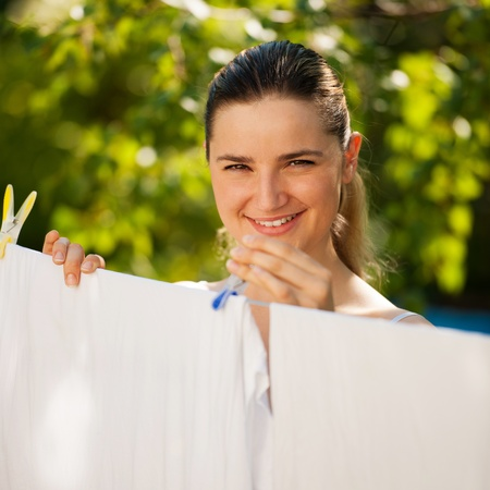 Young beautiful woman hanging laundry outdoor photo