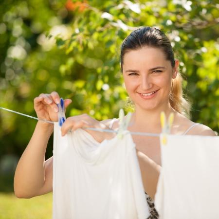ropa colgada: Joven y bella mujer colgando ropa al aire libre