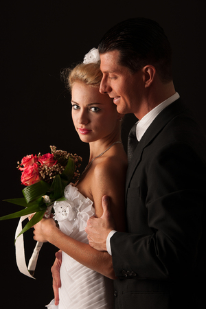 Bride and groom isolated over black background photo