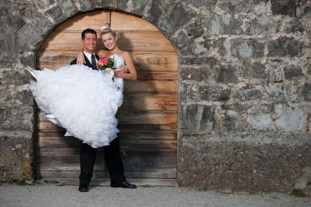 Groom holding a bride infront of wooden door photo