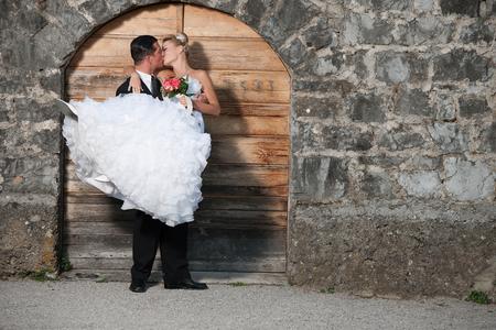 Groom holding a bride infront of wooden door photo