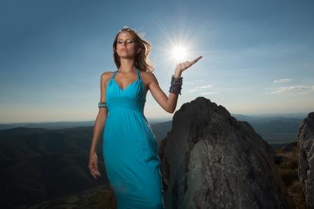 Greek beauty - portrait of a beautiful woman in blue long dress with sun in background