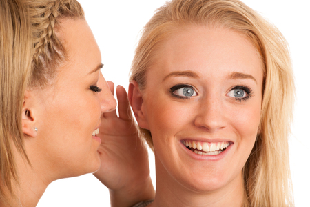 girls chat - woman whispers on friends ear photo
