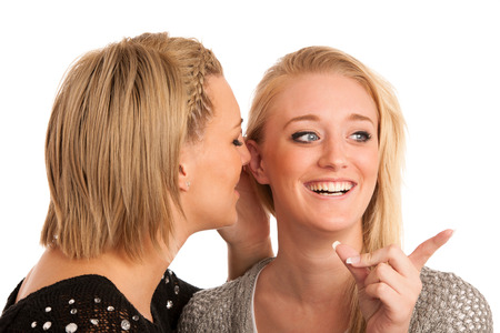 girls chat - woman whispers on friends ear Stock Photo