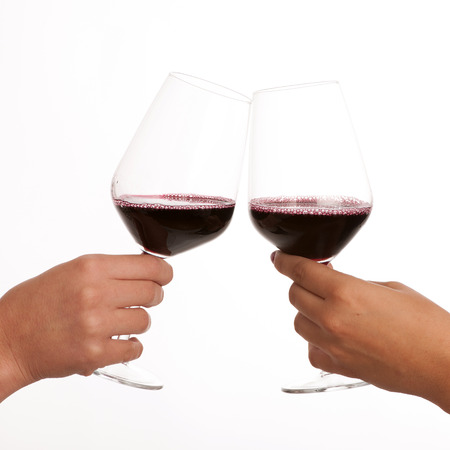 Drinking wine: two glasses of wine in hands isolated over white