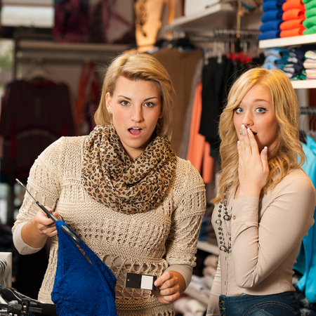 Two girls shocked by a price of clothes in a shop photo