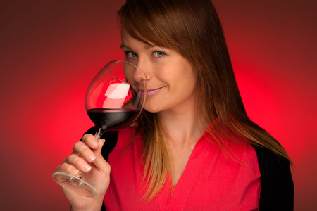 Attractive brunette with a glass of wine over red background photo