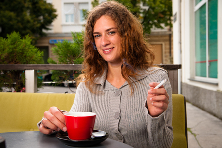 Young woman drinking coffee and smoking cigarette outdoors photo
