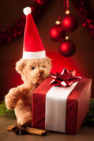 Teddy bear with red santa claus hat and christmas presents photo
