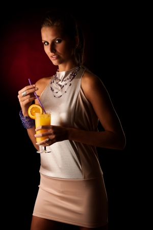 Beautiful young woman with cocktail isolated over black background photo