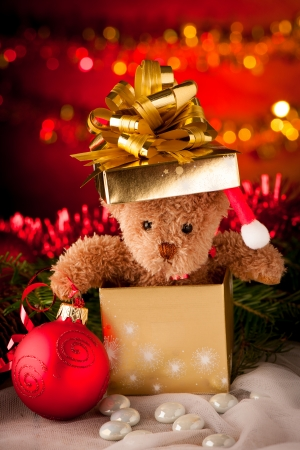 Plush bear in golden present box christmas ornaments with lights in background and red ball photo