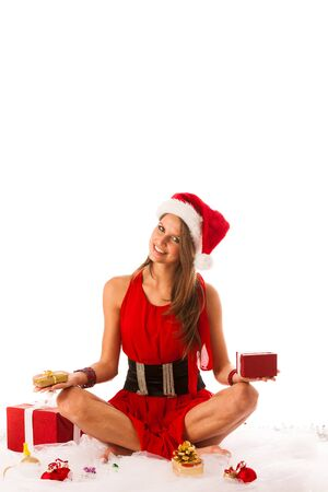 Beautiful young woman in santa claus dress sitting on the flor isolated over white photo