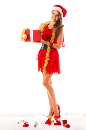 Beautiful young woman in santa claus dress standing isolated over white with christmas presents photo
