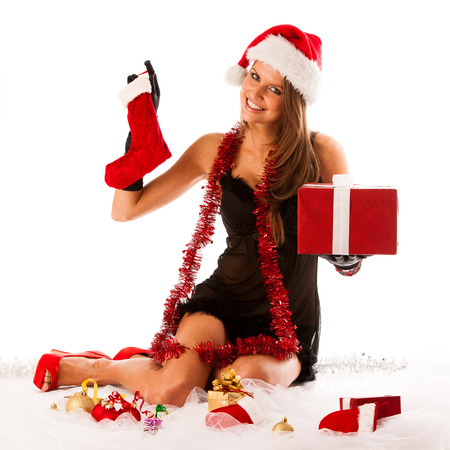 Attractive brunete girl in black dress with santa hat isolated over white background photo