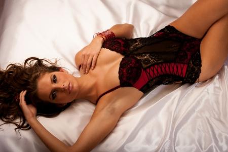 Joven y bella mujer con ropa interior negro y rojo en la cama Foto de archivo