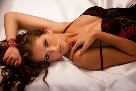 Beautiful young woman wearing black and red lingerie in bed photo
