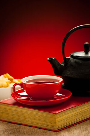 Teapot and tea cup arangement on a table photo