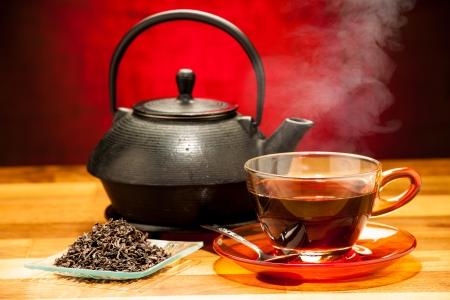 una taza de té negro con la tetera en el fondo