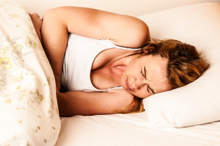 Woman feeling sick with stomachache in bed - havy Pain in stomach Stock fotó