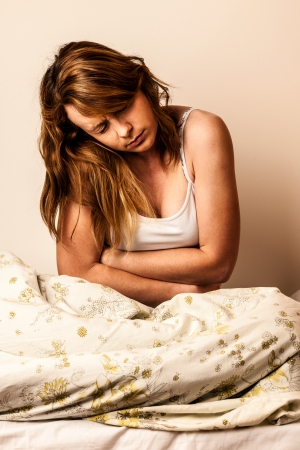 Woman feeling sick with stomachache in bed - havy Pain in stomach Foto de archivo