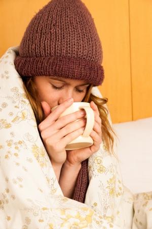 zieke vrouw met feaver drinken kop warme thee onder deken