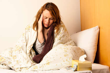 Sick woman with headache in bed - illness photo