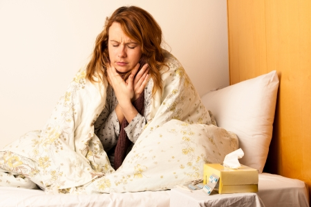 Young woman with sore throat in bed photo