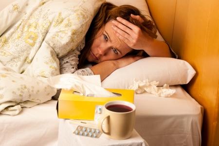 mujer descansando: Mujer joven enferma que se reclina en la cama Foto de archivo