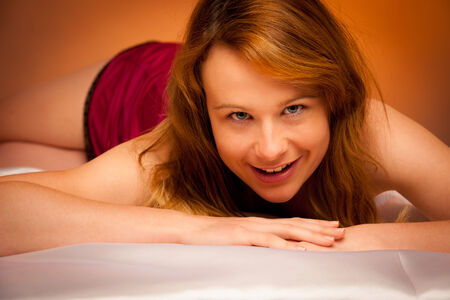 woman in lingerie lying on satin sheets bed in bedroom photo