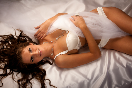 Beautiful young woman wearing white lingerie lying in bed on silky sheets photo