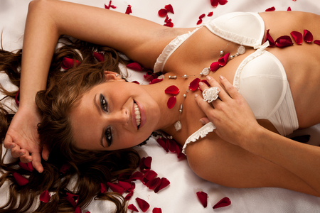 Beautiful young woman wearing white lingerie lying in bed of roses on silky sheets with red rose petals photo